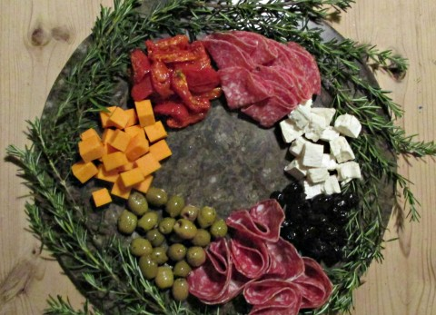 """Antipasto means """"before the meal"""" and is the traditional first course of a formal Italian meal. The wreath itself is formed from sprigs of Rosemary, which looks very festive and is available all year round, but for a summer wreath there would be a whole host of herbs available in the garden to experiment with."""