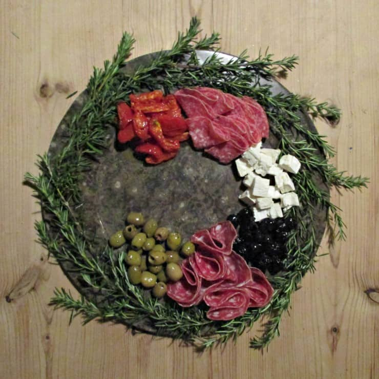 "Antipasto means ""before the meal"" and is the traditional first course of a formal Italian meal. The wreath itself is formed from sprigs of Rosemary, which looks very festive and is available all year round, but for a summer wreath there would be a whole host of herbs available in the garden to experiment with."